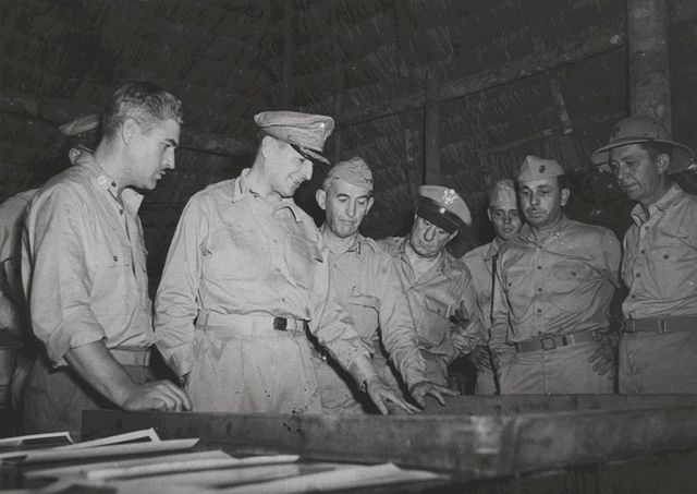 man in military uniform looks at maps with soldiers