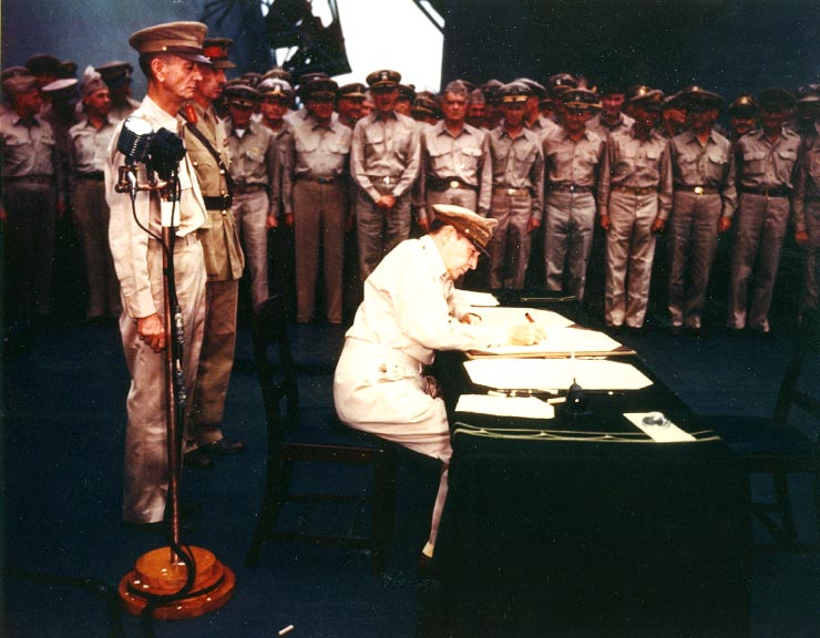 man in military uniform signs document in front of soldiers