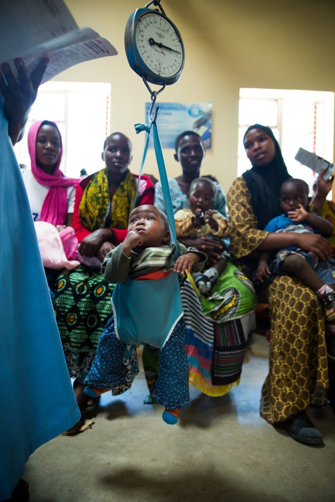 A baby is weighed in a hanging scale at the Makiungu Hospital with mothers from the community watching