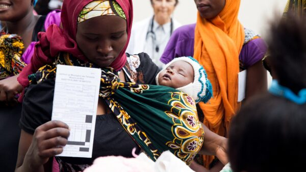 A woman holds her newborn baby and her monthly ration card