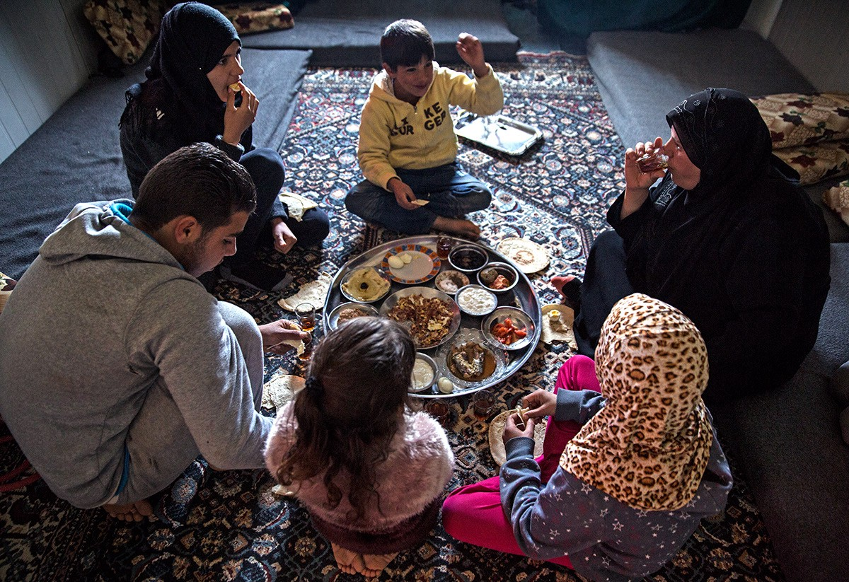 Marouf's family enjoys a meal together after returning from the Tazweed market.