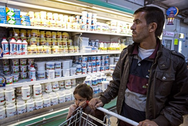 Marouf buys groceries with Noor from Zaatari's Tazweed market purchased using WFP's e-cards.