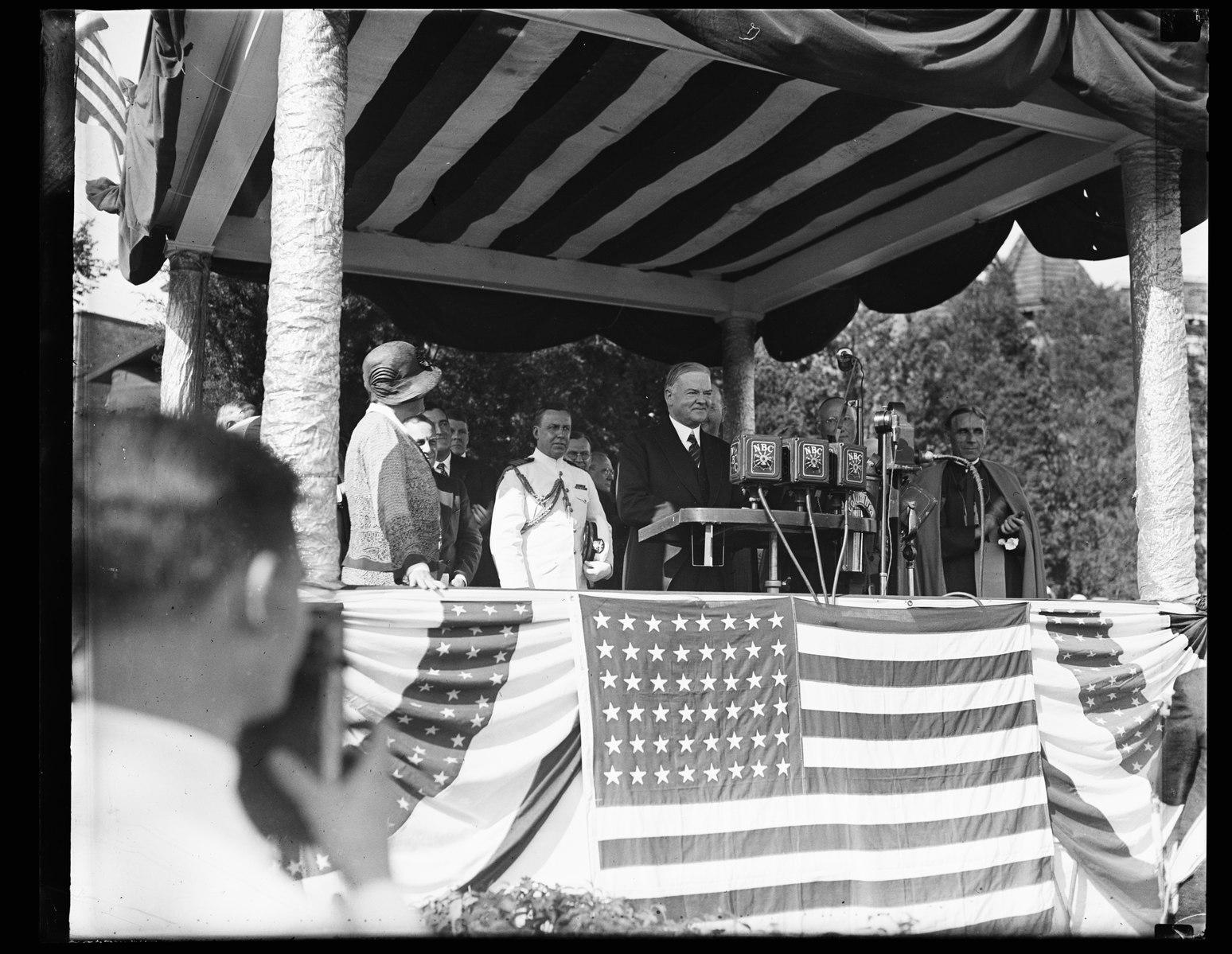 man speaking on gazebo with American flags