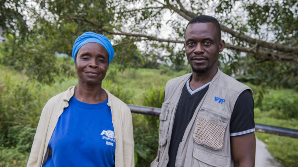 Pauline and Aaron stand in front of the camera, they are helping with the Ebola emergency