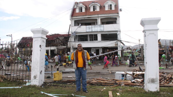 Praveen Agrawal stands outside of damaged buildings after Typhoon Haiyan in the Philippines