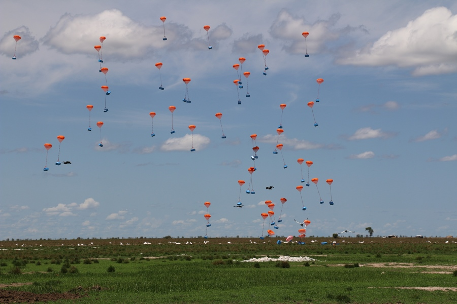 Vegetable oil floats down from the sky in red parachutes