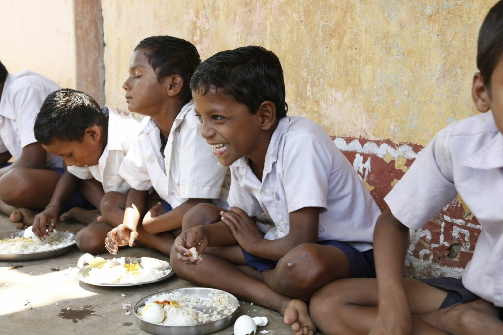 Children sit on the ground eating fortified rice and hardboiled eggs