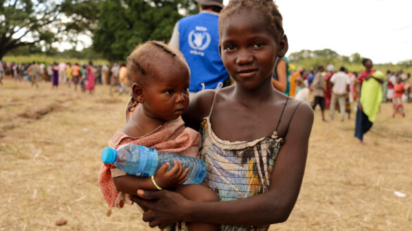 A young girl holds her baby sister during a WFP food and nutrition distribution in Farajallah, South Sudan.