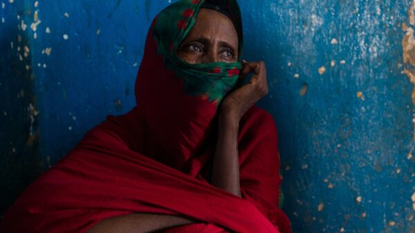 A Somali woman covering her lower face with her red hijab. Staring into the right on a blue wall.