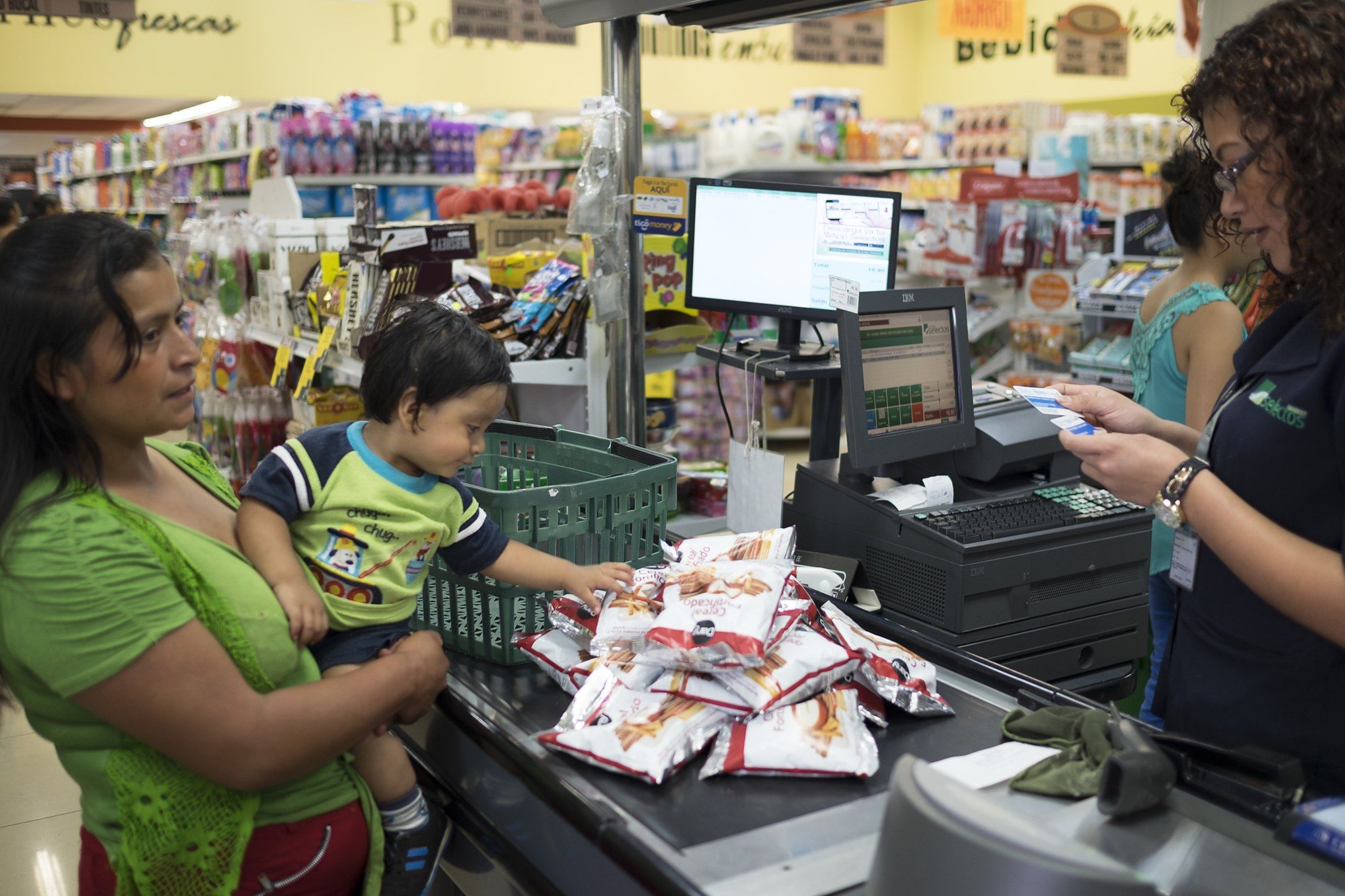A woman stands at the checkout line with her baby in her arms, while the cashier checks her e-card