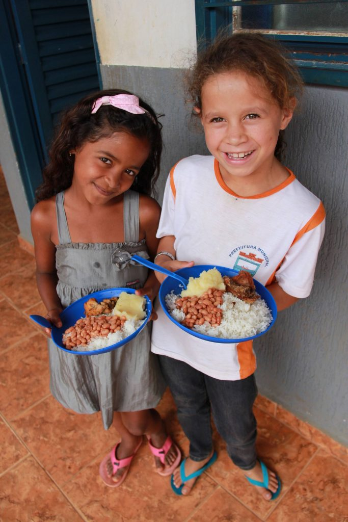 Students in Brazil hold up plates full of rice, beans and cassava from WFP.