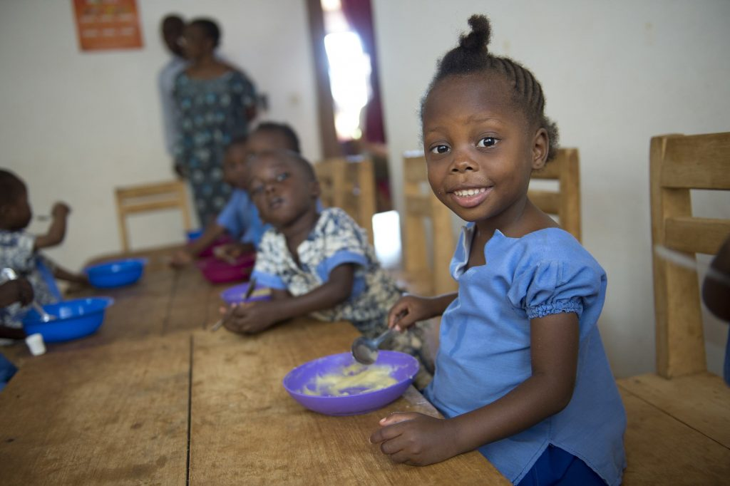 A young girl named Dieu-Merci smiles at the camera while eating her meal in the orphanage