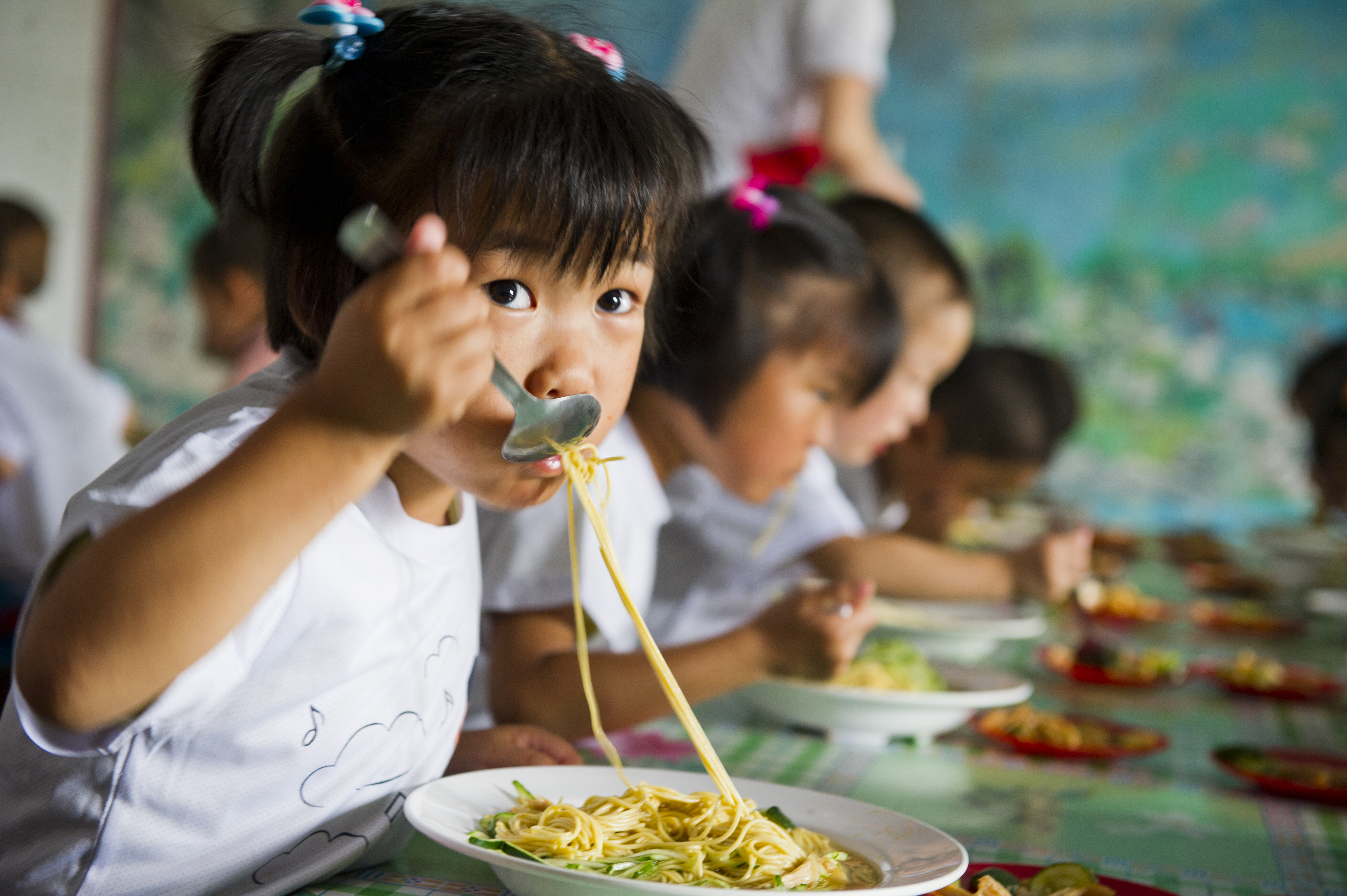 A young girl slurps her meal of noodles