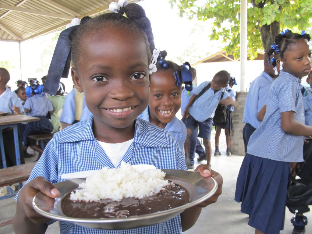 A young girl shows holds up her plate of rice and beans