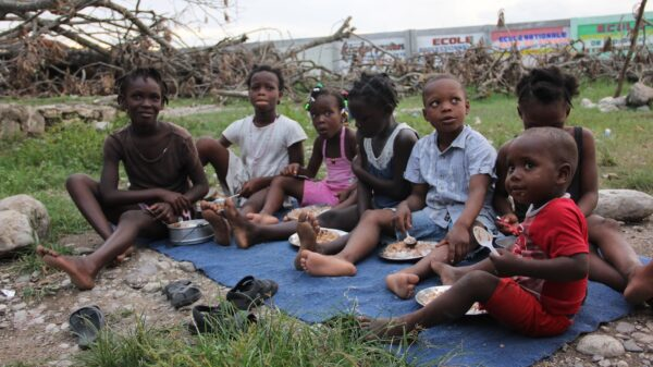 In hurricane-ravaged town of Torbeck, Haiti, a group of children gather around a meal of rice, peas and vegetables provided by WFP in the aftermath of Hurricane Matthew.