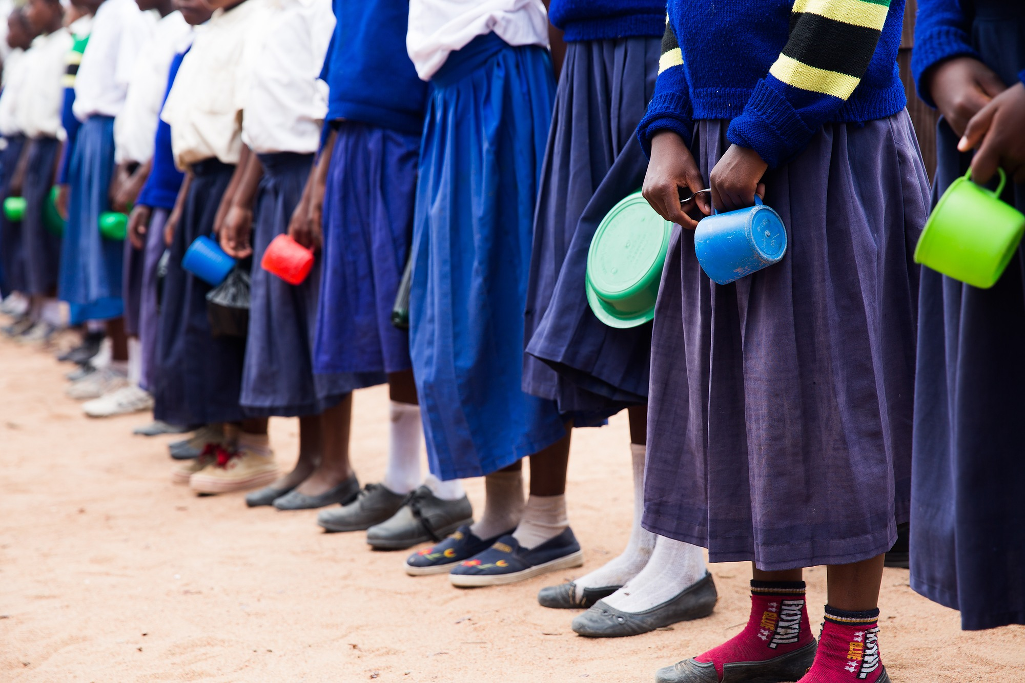 Students lined up, seen from the waist down, holding bowls and cups in their hands