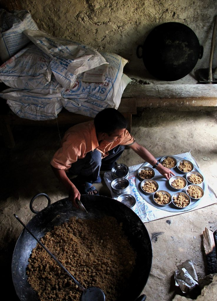 A cook prepares school meals in Nepal using WFP's fortified grains to meet a child's daily dietary needs