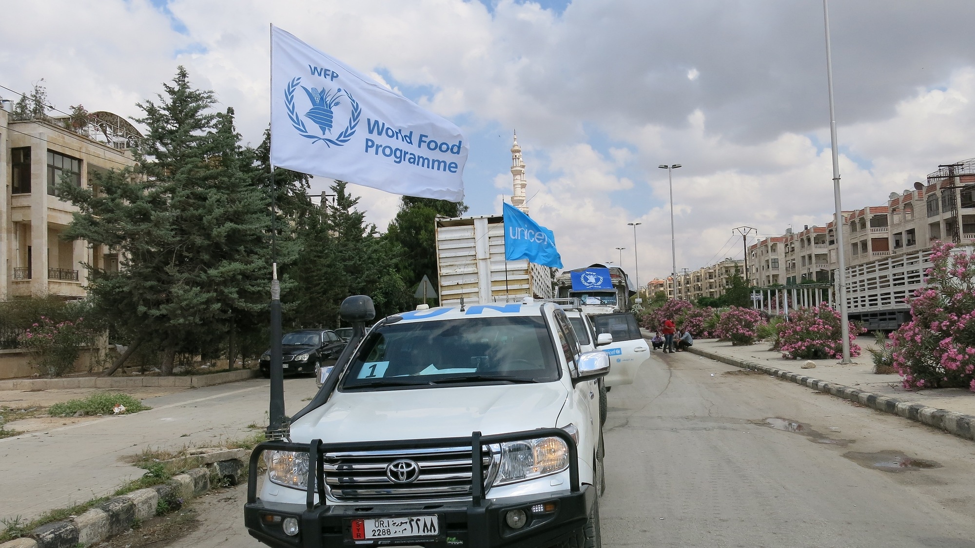 A convoy of trucks with WFP and UNICEF flags