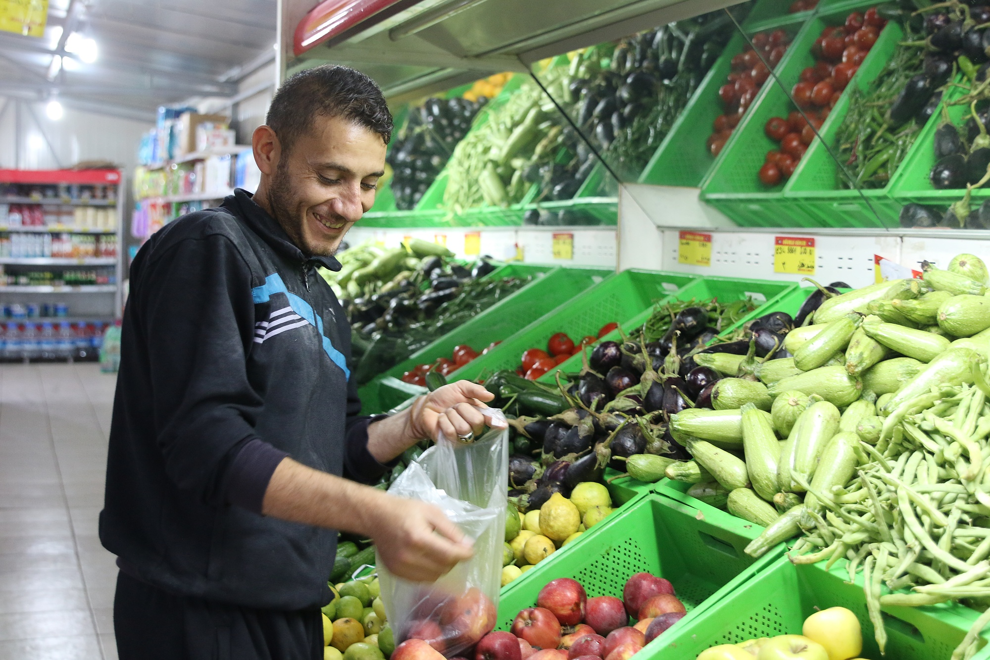 Nidal shops for vegetables in the supermarket of the Boynuyogun refugee camp in Turkey