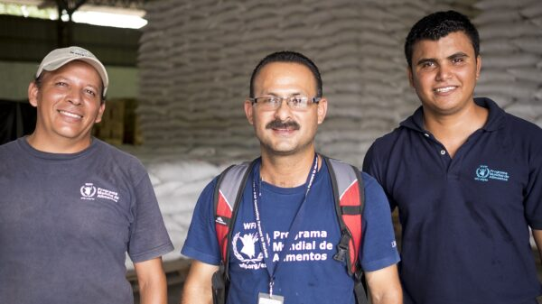Three men look at the camera, Carlos Sorriano in the center, with WFP bags behind them