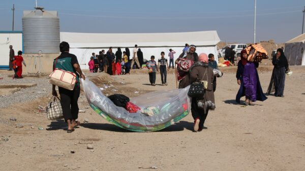 A man and woman carry blankets and other belongings into the Hassan Sham camp of Iraq