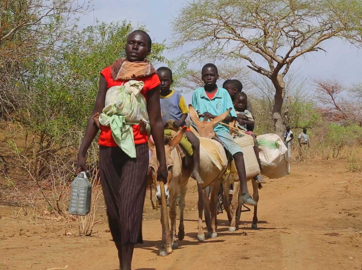 Apu Riang's family walk in a line through the South Sudanese bush