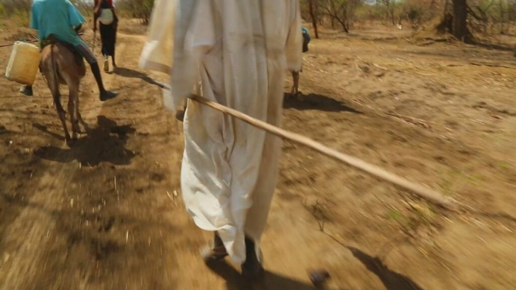 Apu Riang walks through the South Sudanese bush with a spear in hand