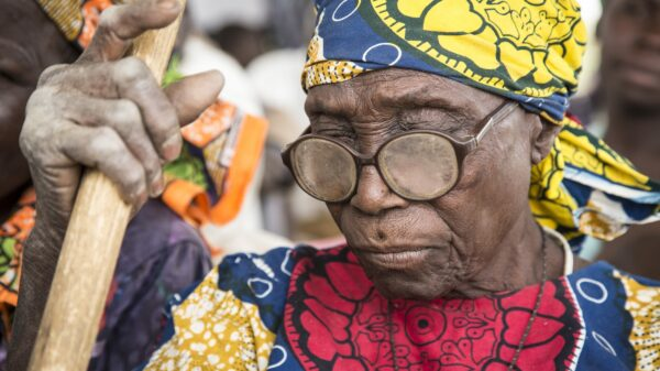 A woman wearing dirty eyeglasses and holding a walking stick looks down while waiting at a food distribution