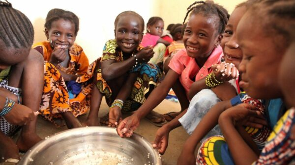 A group of smiling young girls gathers around a large bowl of food