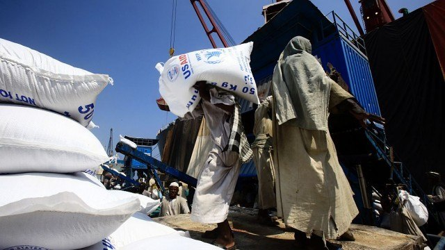 People carrying WFP/USAID bags of food assistance