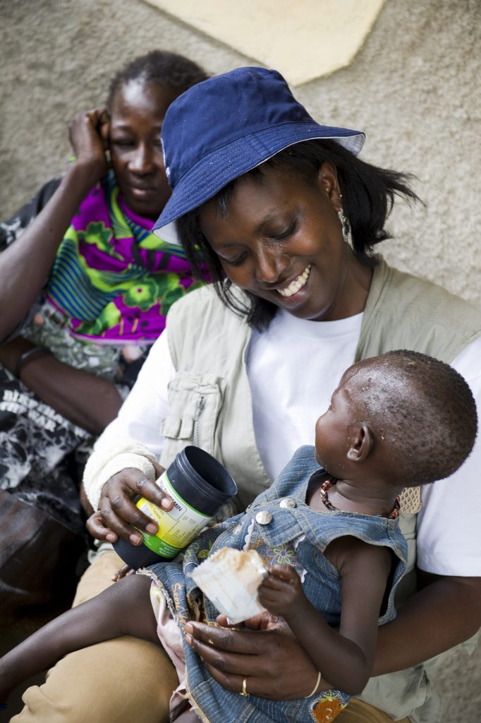 Then WFP staffer Rose Ogola helps 18 month old Onrika Nawet drink some water in Turkana, Kenya. Photo: WFP/Rein Skullerud