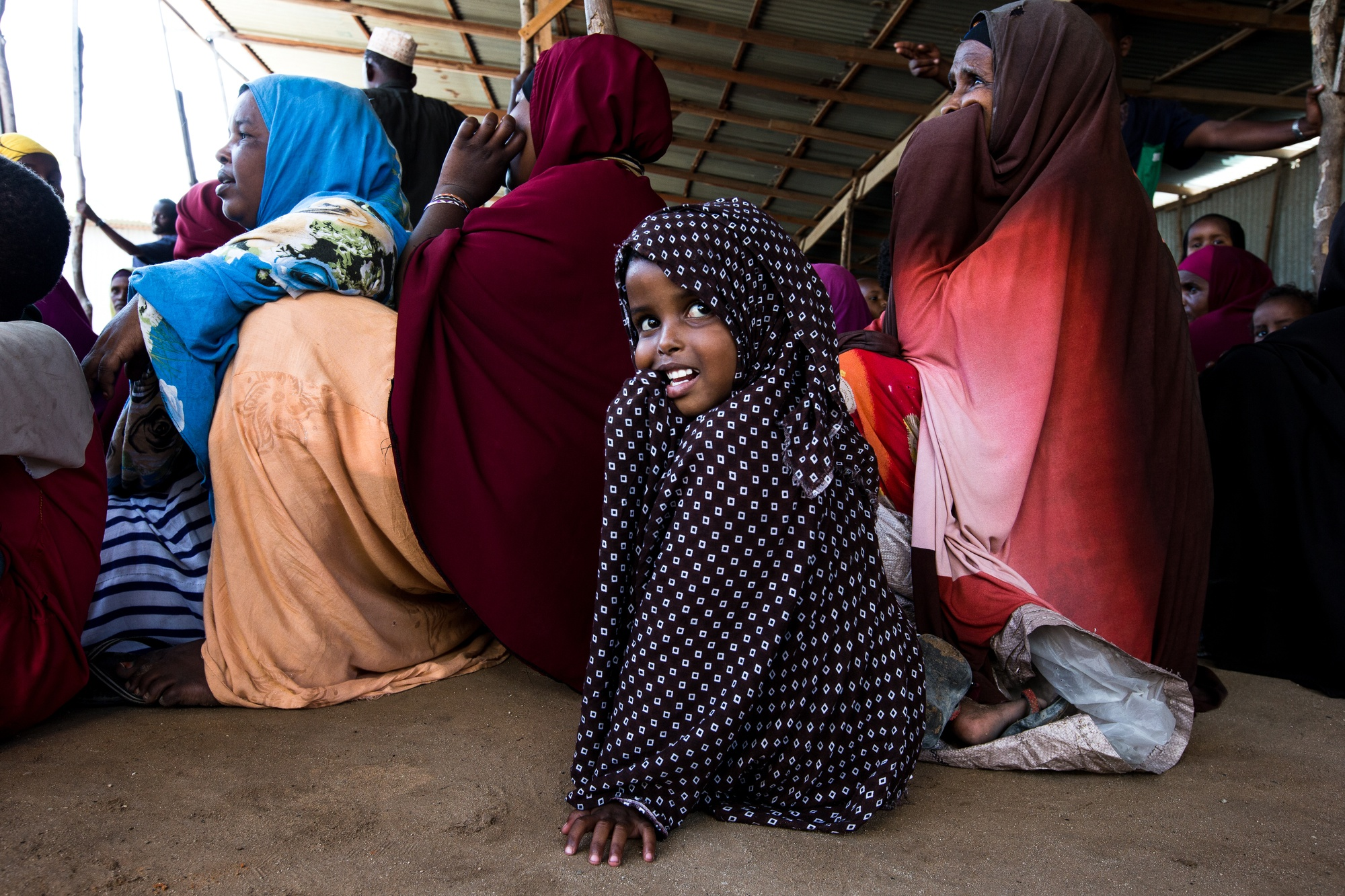 A young girl sits in a line at a food center, wearing a polka dot hijab over her head