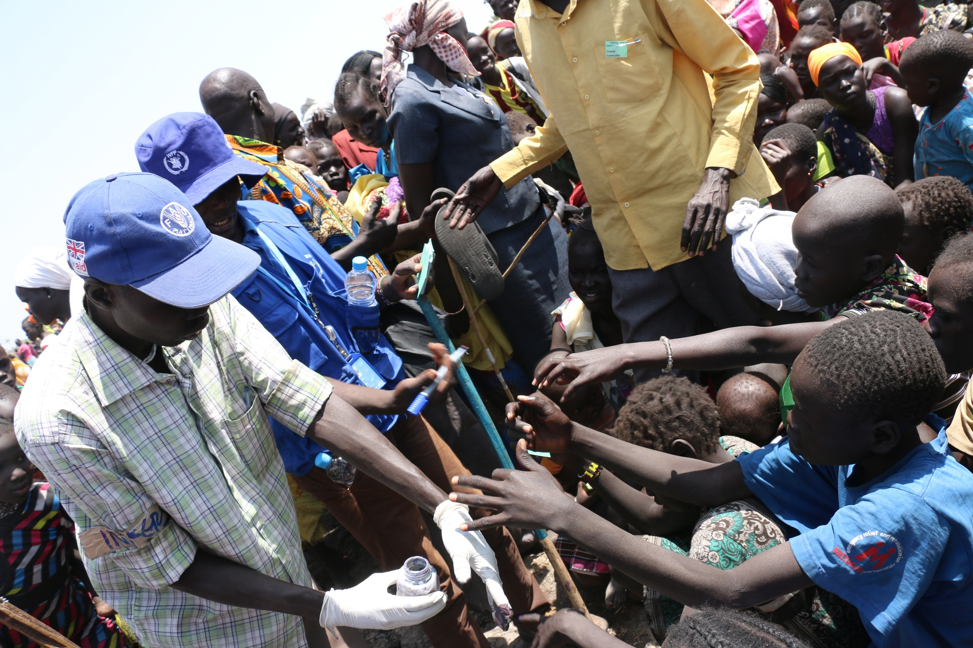 A WFP staffer is surrounded on all sides by people with children reaching out to him as he puts ink on their hands