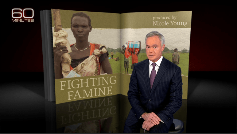 "Scott Pelley sits in front of a screen that says ""Fighting Famine"" and features the face of a woman"