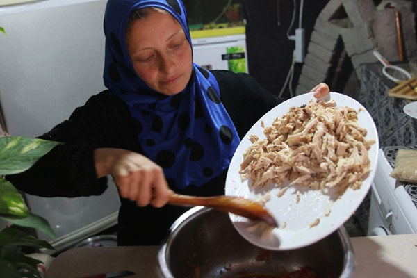 A Syrian woman named Najla cooks chicken kabsa for her family in Turkey's Boynuyogun refugee camp.