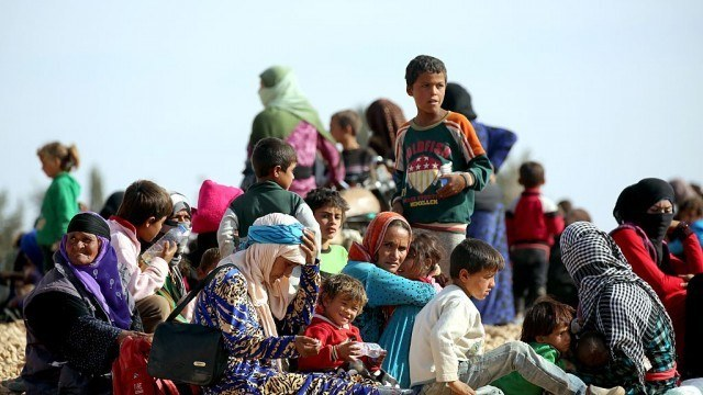 Syrian Refugees wait for food