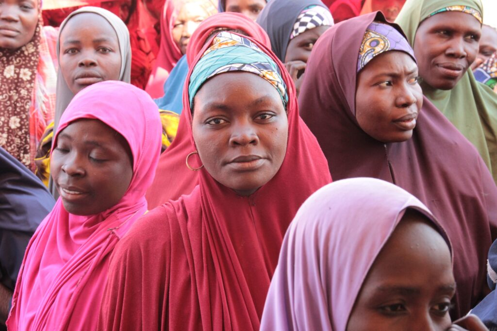 Women at a food distribution center in Nigeria, all wearing brightly colored hijabs on their heads