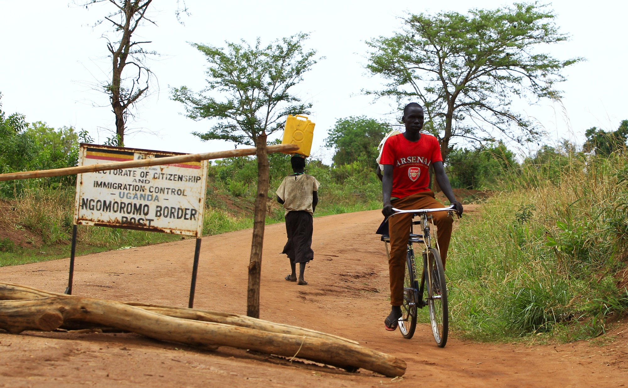 A man rides a bike past a sign indicating the border