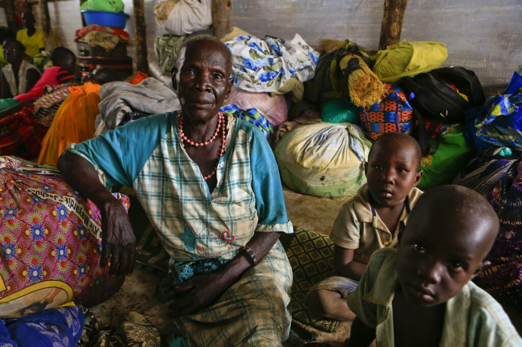Abeer sits wearing a blue and white plaid dress alongside her two grandchildren in a tent filled with belongings of families who fled their homes in Pajok, South Sudan