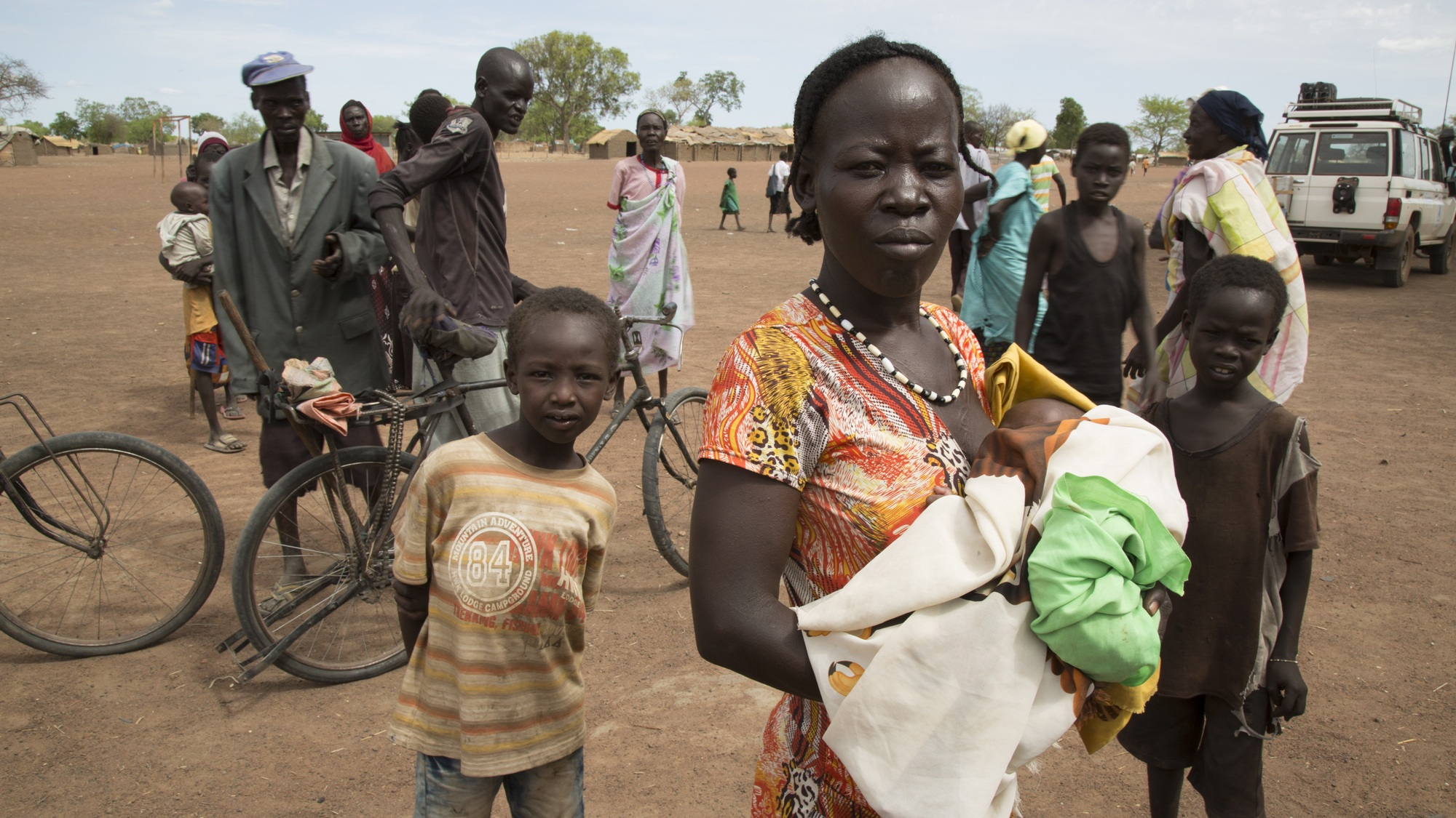 A woman holds a bundled baby in her arms and looks at the camera, other people and their bikes stand behind her