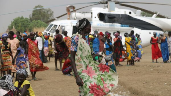 Women at a food distribution point with a WFP-chartered helicopter in the background