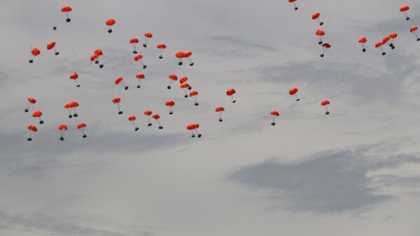 Lots of red parachutes attached to food boxes and bags float through the sky
