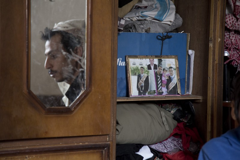 Walid's reflection is seen in a mirror, his graduation photo is propped up on a closet shelf next to it