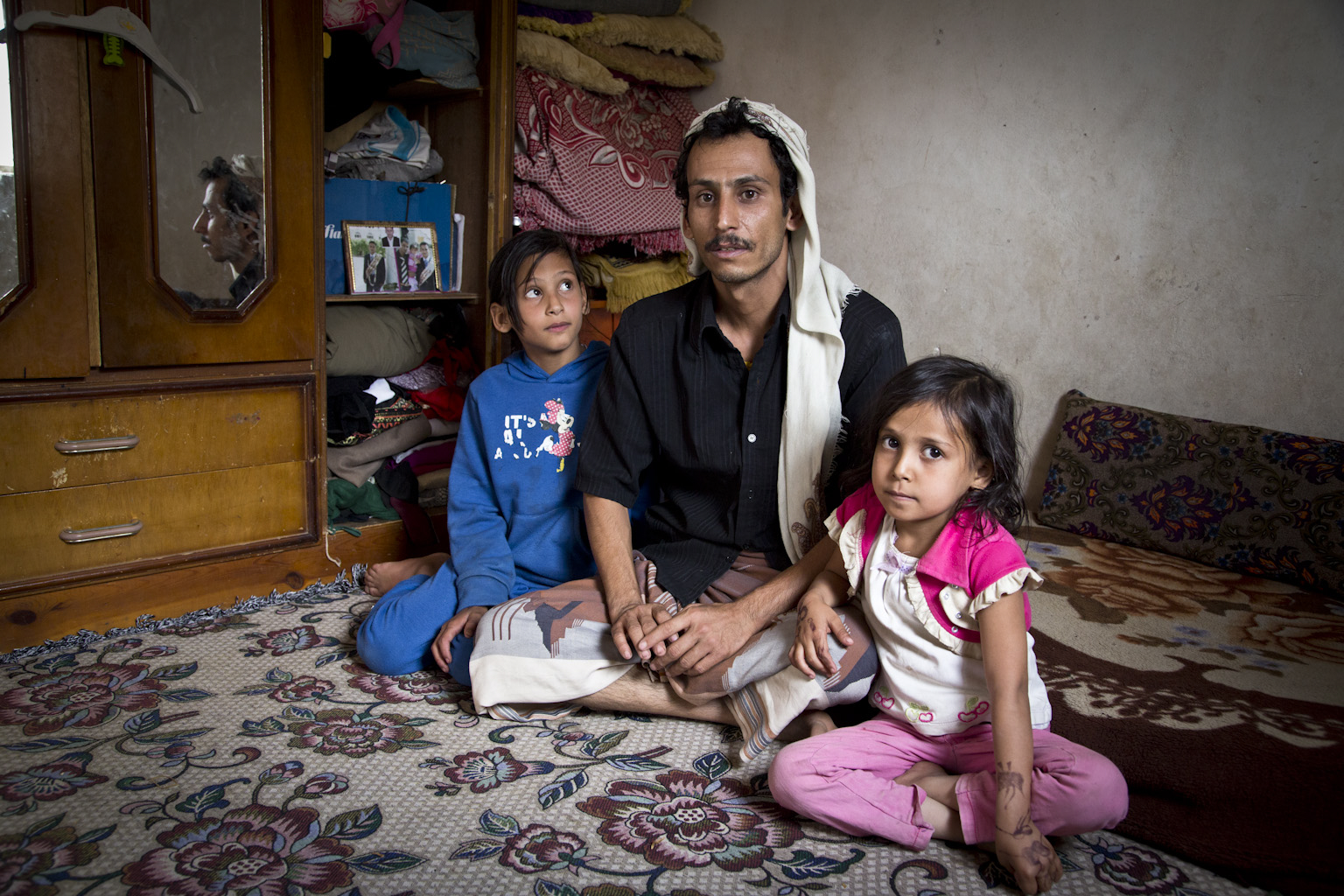 Walid sits with his two daughters on the floor, one daughter looks up at him