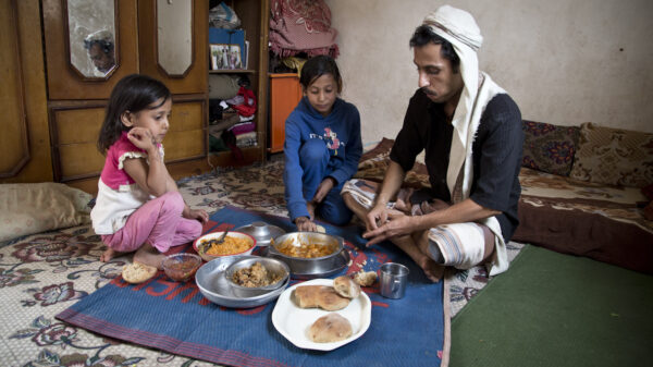 Walid and his two daughters sit on the floor with a blue mat covered in food dishes