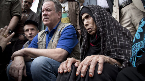 David Beasley sits next to an older woman wearing a black and white checkered hijab