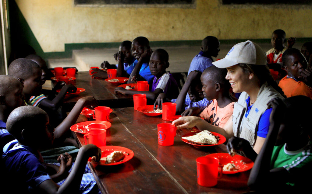 World champion swimmer Natalie Coughlin shares a meal with students at Uganda's Moroto Primary School during a trip with World Food Program USA as the organization's newest ZeroHunger Ambassador.