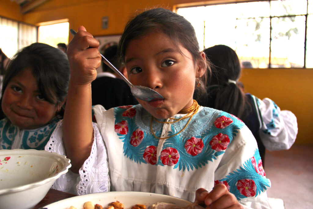 a young girl eats a meal at school