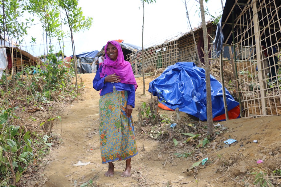 Rahima stands in front of the settlement of tarps and bamboo sticks