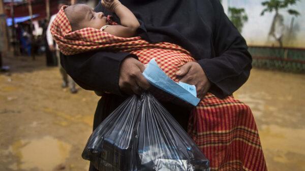 A mother holds a baby in her arms as well as a bag of biscuits